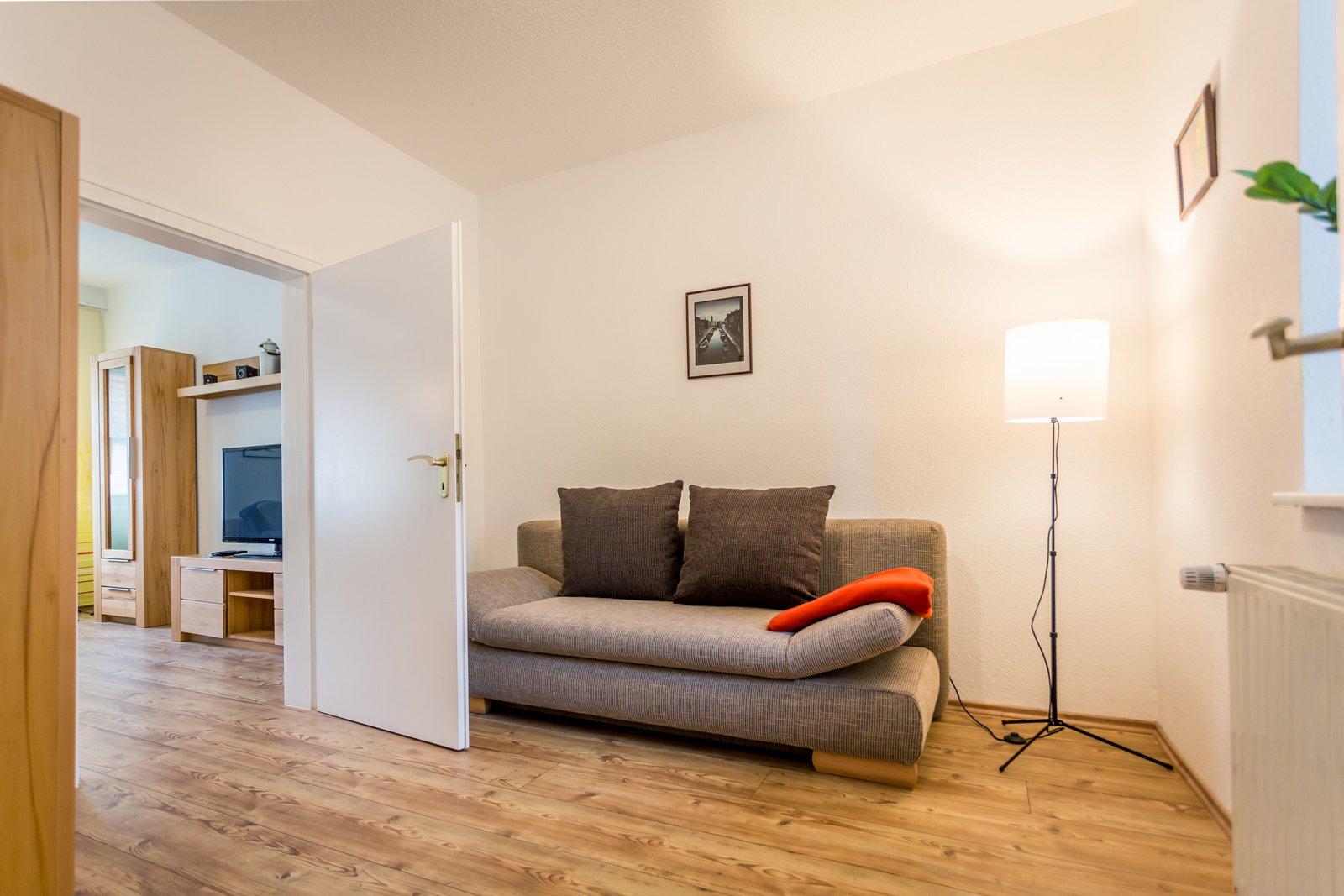 Graue Couch in hellem Raum mit gemütlichem Lich einer Stehlampe