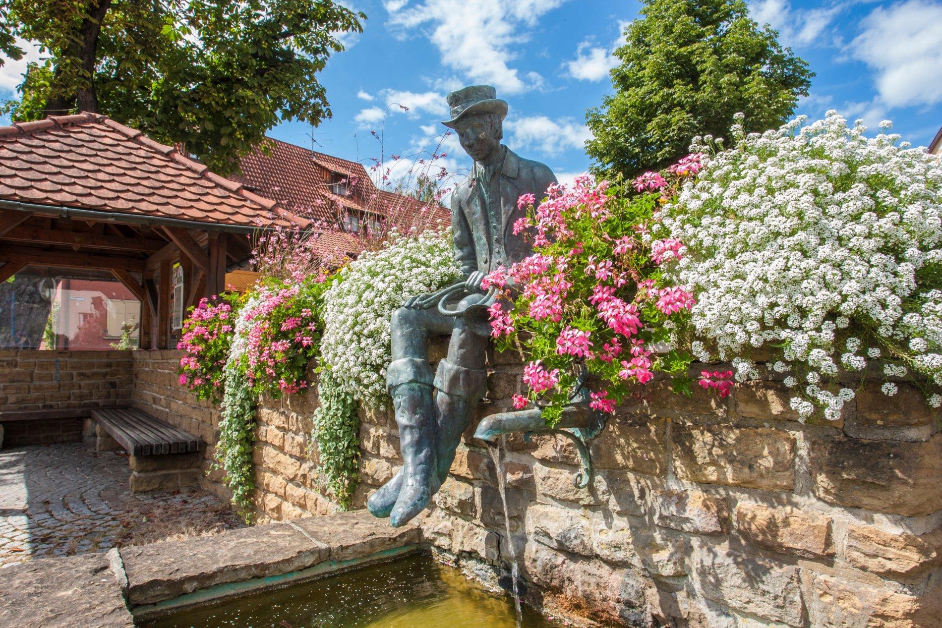 Brunnen mit Blumen und der Skulptur eines Mannes