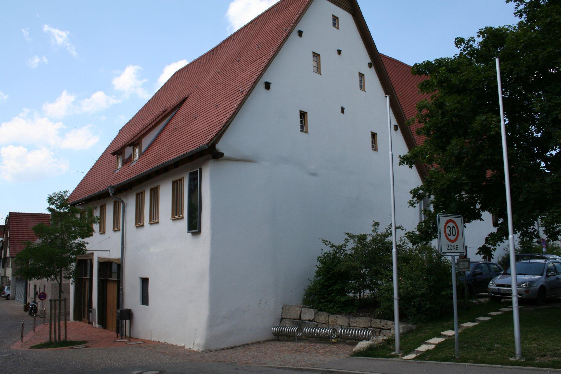 Historisches Gebäude, vor dem Eingang steht ein Baum
