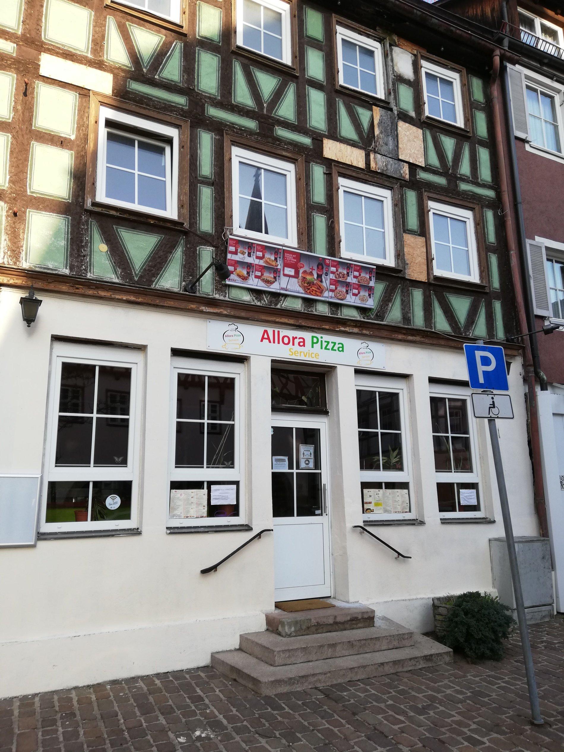 Eingang des Allora Pizza Abholservice, neben der Eingangstür sind rechts und links 2 Fenster