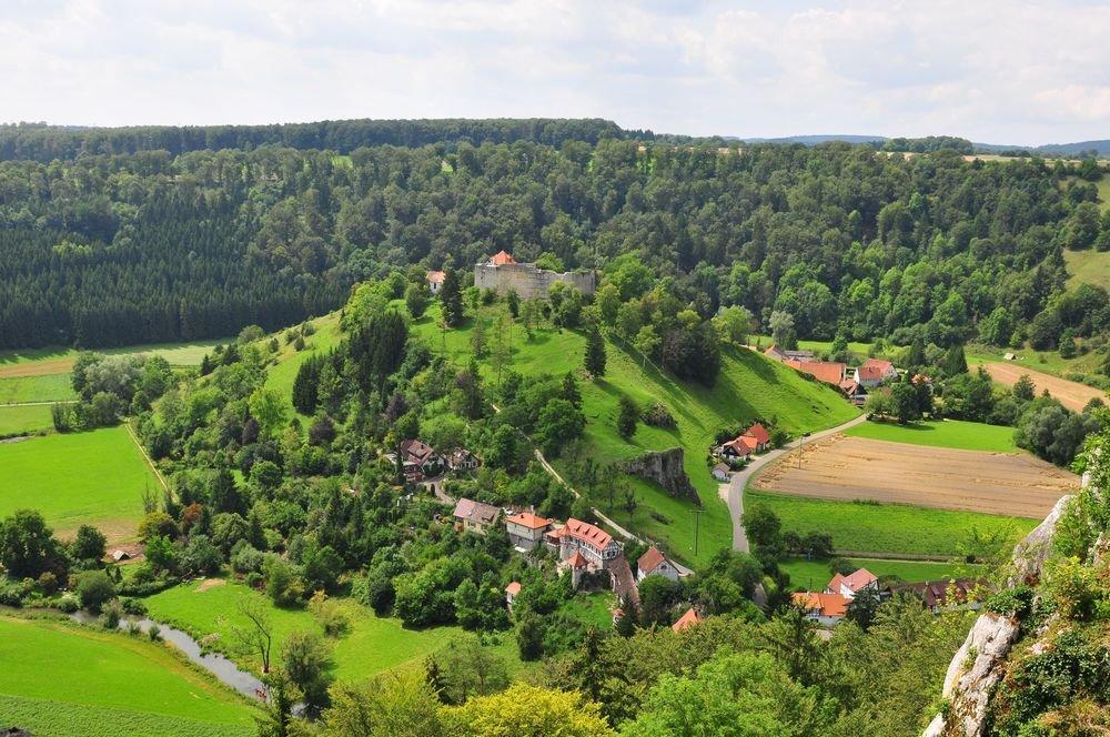 Auf einem Hügel ist eine Burgruine mit massiven Steinmauern. Dahinter blitzt ein rotes Dach hervor. Unten am Fuß des Hügels liegt ein kleines Dorf und ein Fluss fließt hindurch. Ringsherum sind grün leuchtende Wiesen und Wald. Der Himmel ist bewölkt.