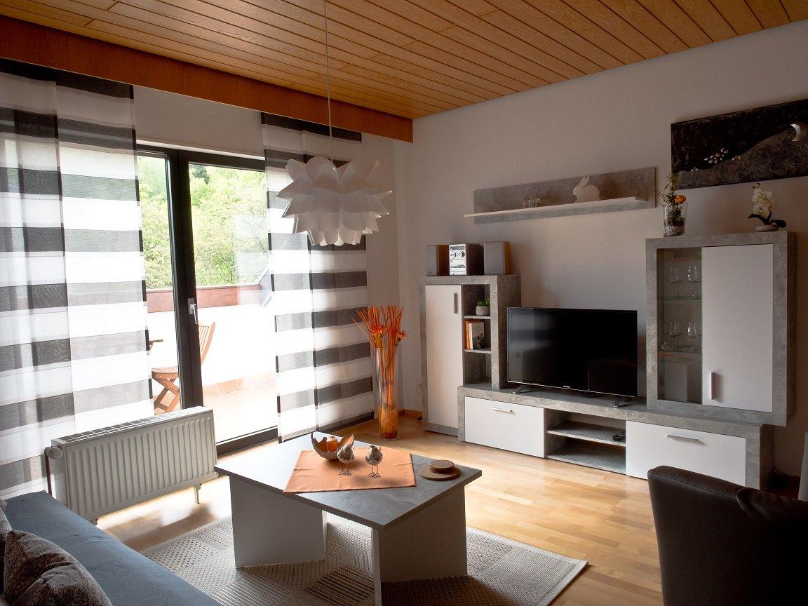 Wohnzimmer mit Fernsehwand und großer Fensterfront