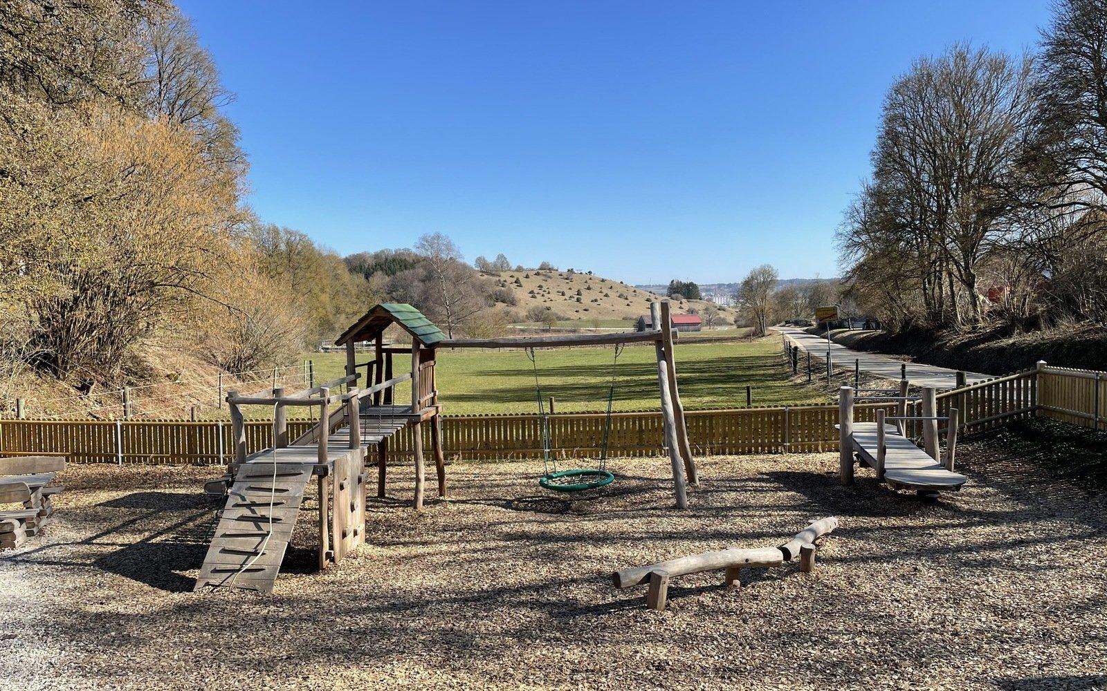 ein Spielplatz, auf der linken Seite ein Spielturm mit Brücke und grünem Dach auf der rechten Seite ein Holzsteg