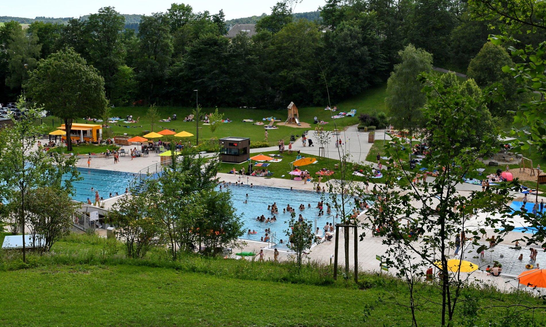 Ein Freibad mit einem großen Becken, einer Wasserrutsche, einem kleinen Kinderbecken, einem Wasserspielplatz, vielen Liegewiesen, einem Kiosk und weiteren Spielmöglichkeiten. Überall tummeln sich Leute. Im Hintergrund sind Bäume.