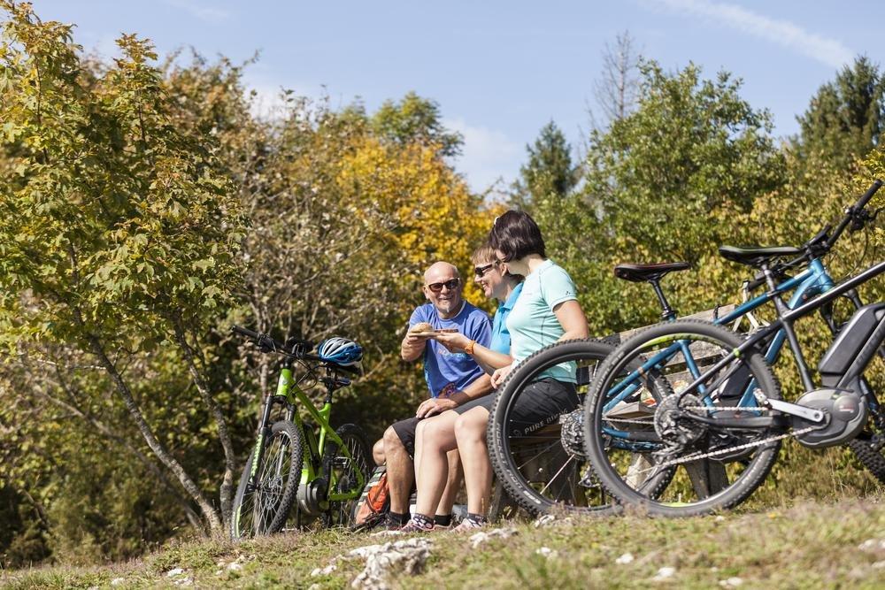 Drei Radfahrer*innen sitzen auf einer Holzbank und machen eine Pause. Die E-Bikes stehen daneben. Eine Person reicht ein Teller mit Essen. Im Hintergrund ist der Herbstwald. Es ist sonnig und warm.