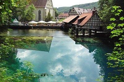 Ein türkisblauer See in dem sich die Wolken, Bäume und Häuser drumherum spiegeln. Auf der anderen Seite ist eine Mühle und einige Sonnenschirme mit Sitzmöglichkeiten.