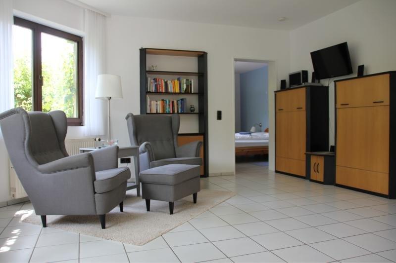 Wohnzimmer mit zwei Lesesesseln und Bücherregalen