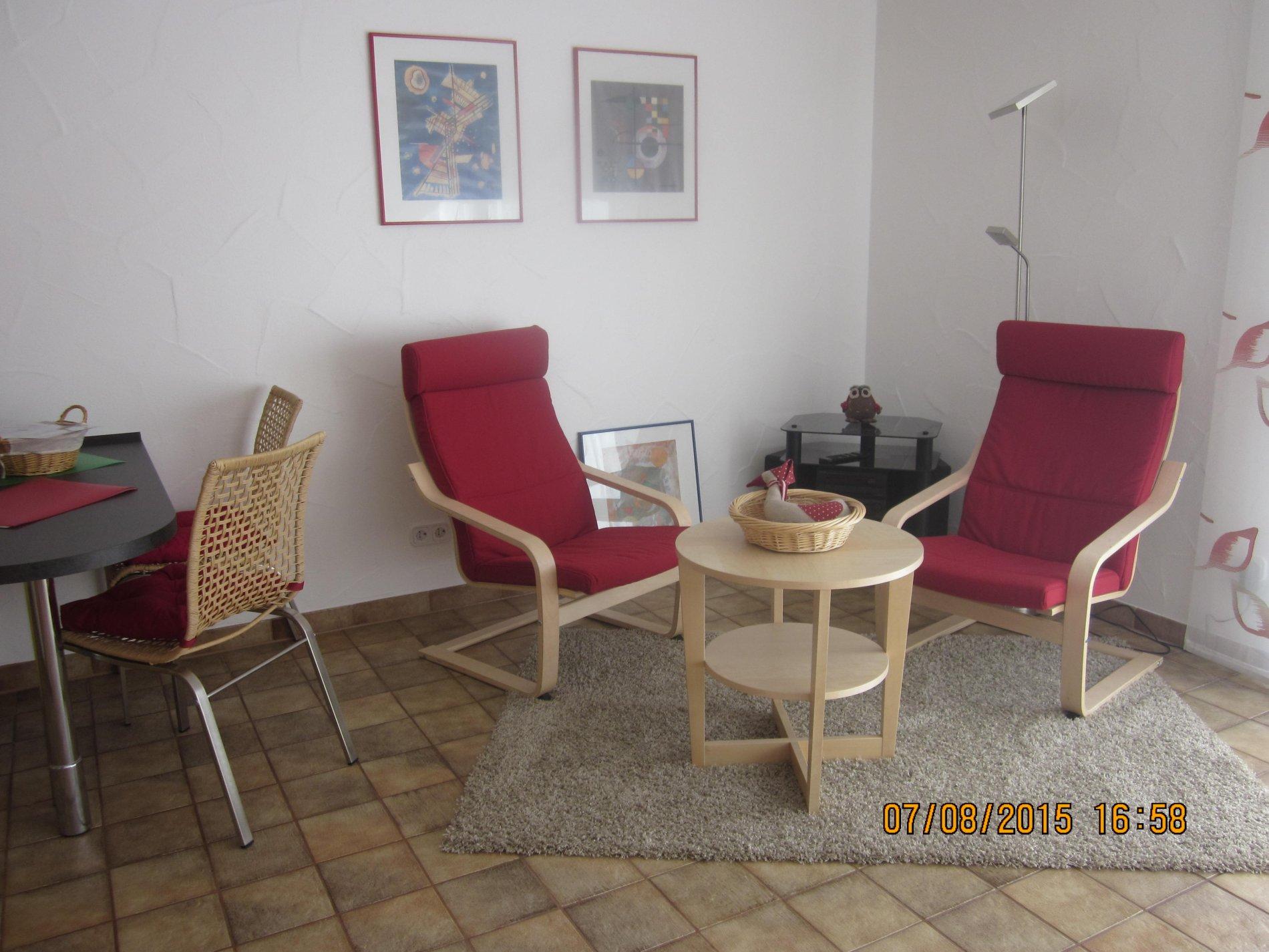 Zwei rote Sessel mit Couchtisch und hellem Teppich