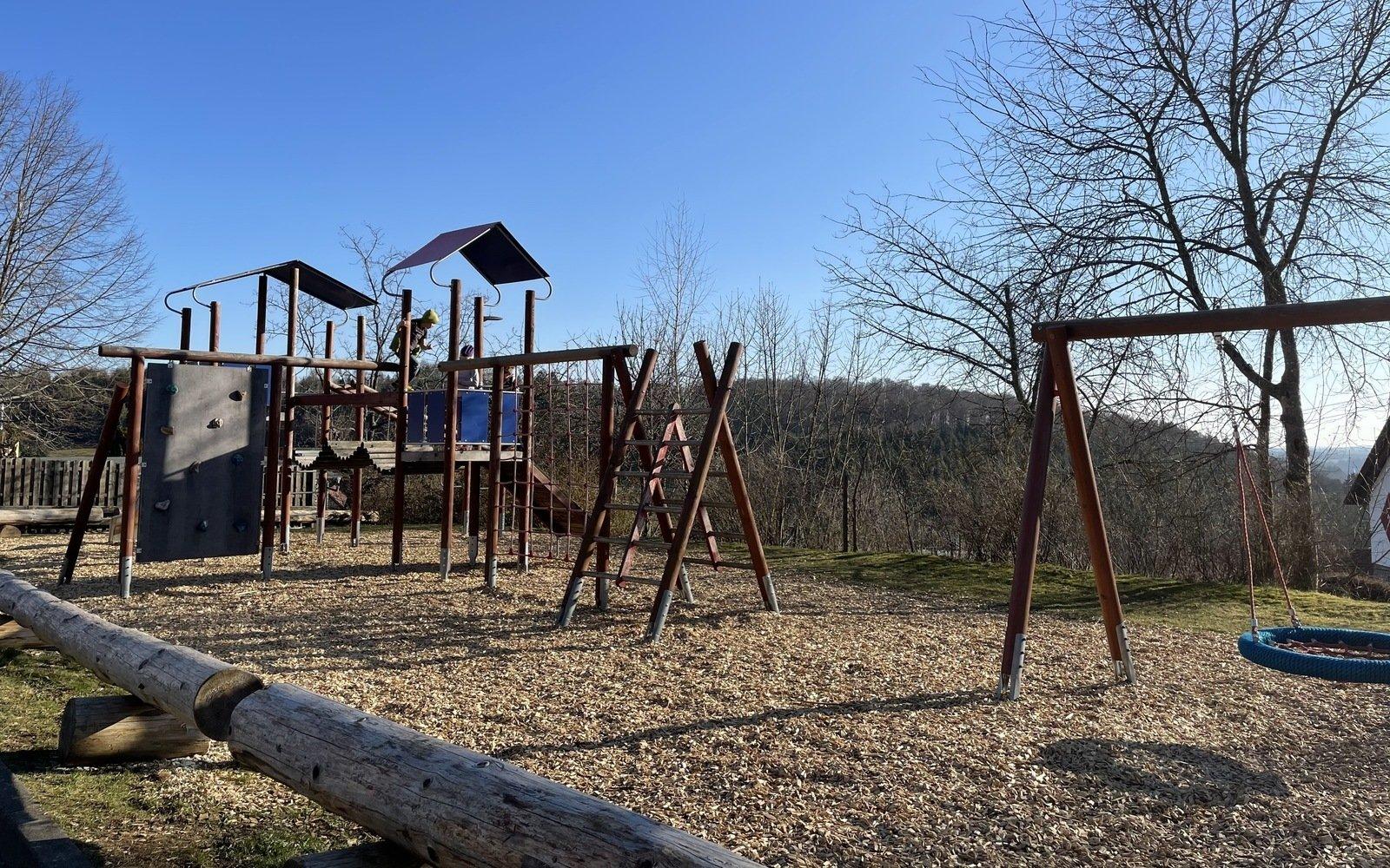 auf einer Anhöhe ist ein Spielplatz mit verschiedenen Spielgeräten wie Klettergerüst bzw. Turm, eine Schaukel umzäunt von Baumstämme