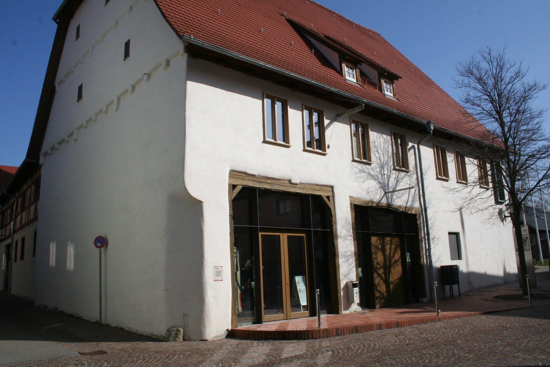 ein großes weißes Gebäude mit einem roten Dach auf der Vorderseite sind zwei große Glastüren