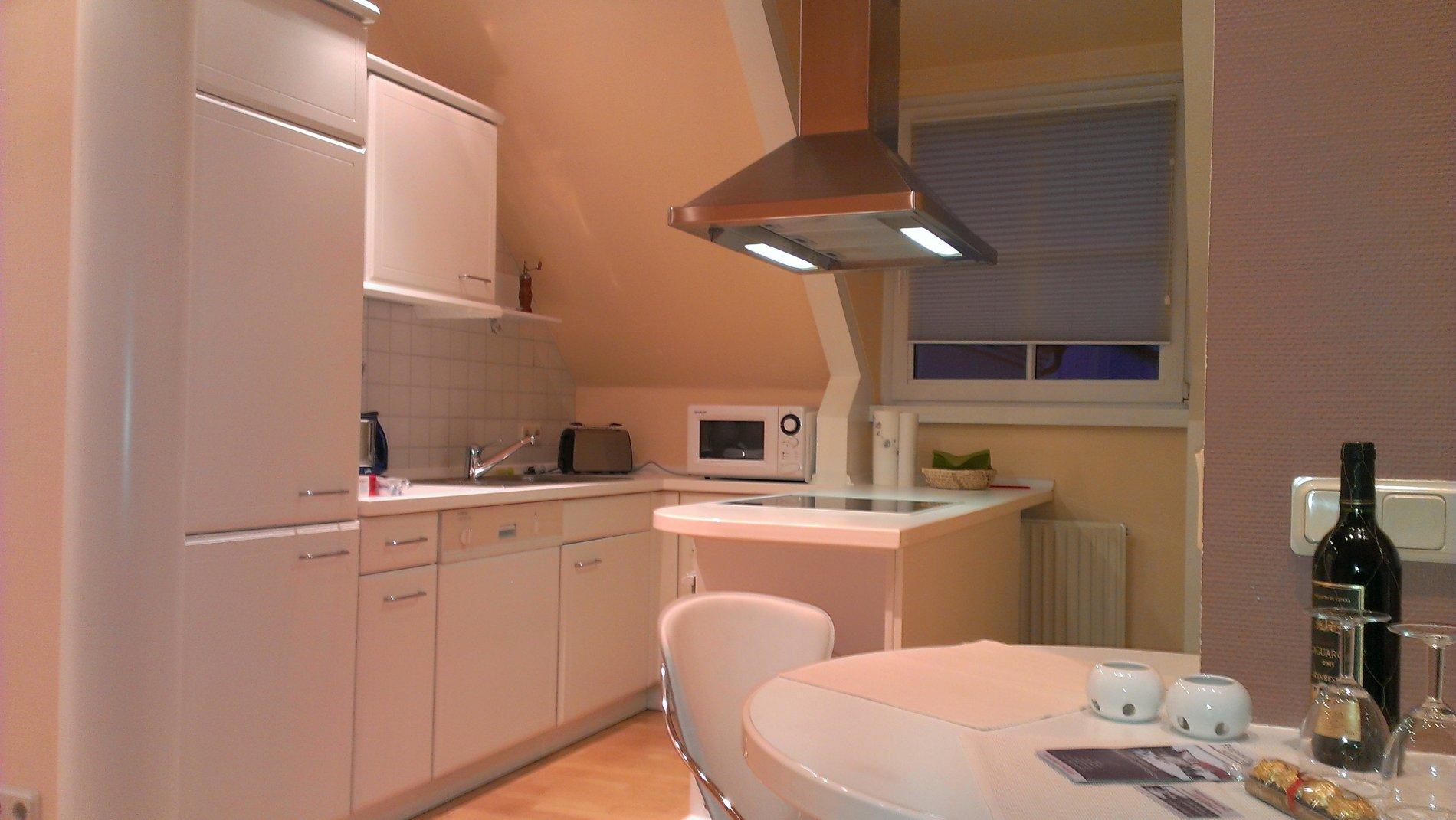 Küche mit Mikrowelle, Toaster, Herd, runder Tisch und Stuhl