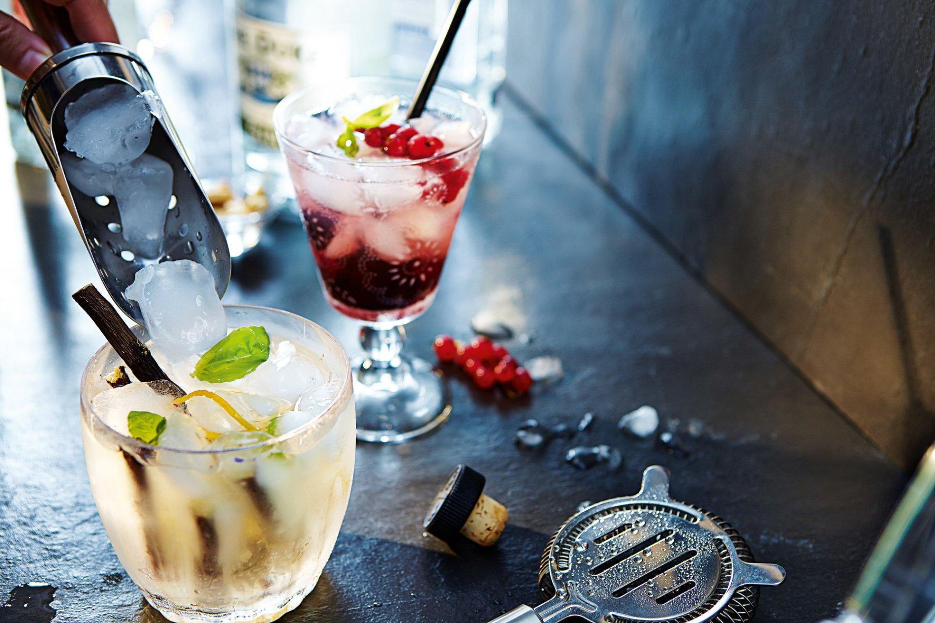 Ein Tisch mit zwei Gläsern mit bunten Cocktails. Eine Person befüllt ein Glas mit Eiswürfeln.
