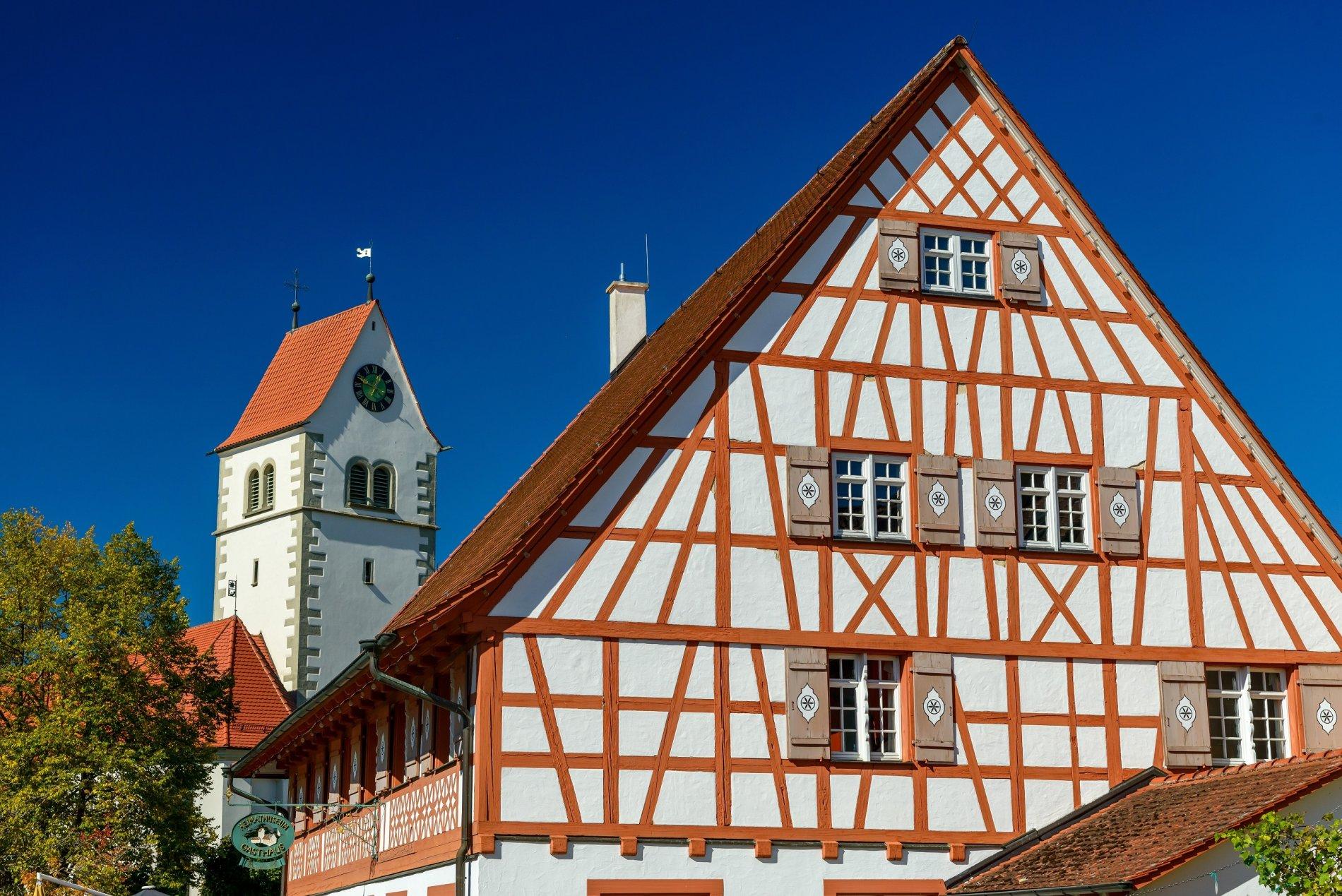 Fachwerkhaus mit Kirchturm im Hintergrund