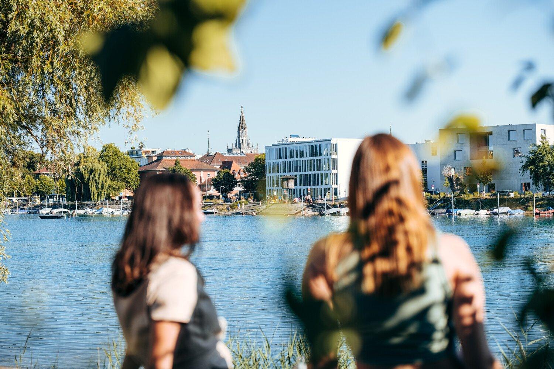 Eine Gruppe genießt den Sonnenuntergang an der Seerhein Promenade.