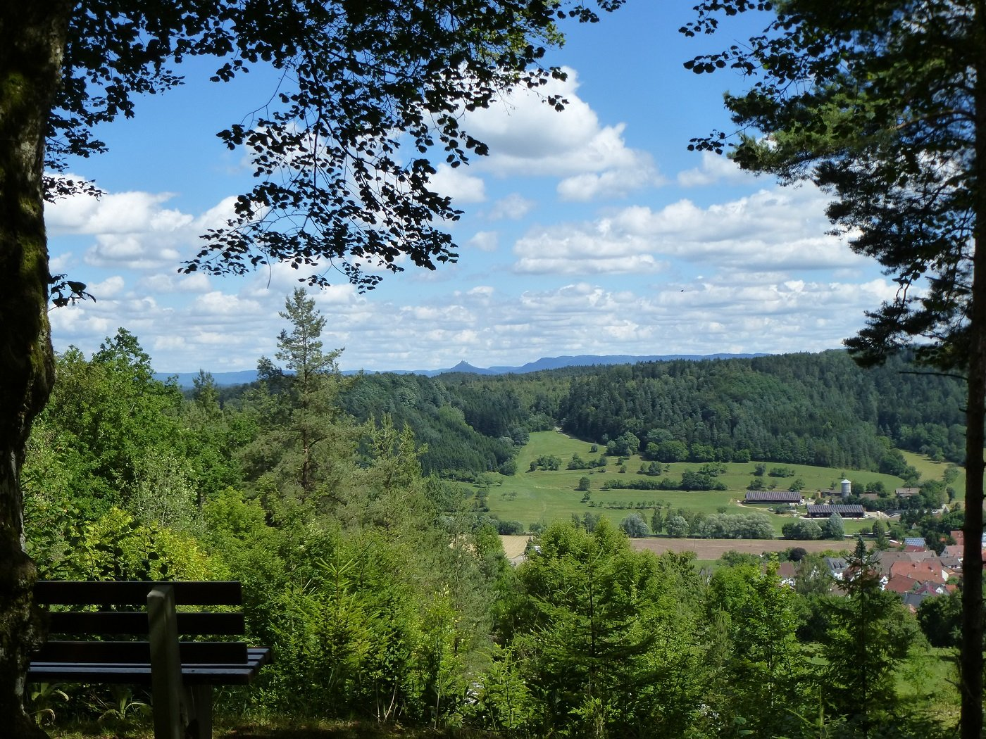 Blick vom Aussichtspunkt Zollernblick aus über Wiesen und Wälder auf die Burg Hohenzollern