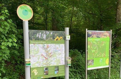 Zwei Wanderparkplatzschilder. An dem größeren von beiden befinden sich Prospekthalter und ein Wegweiser. Im Hintergrund ist ein Wald.
