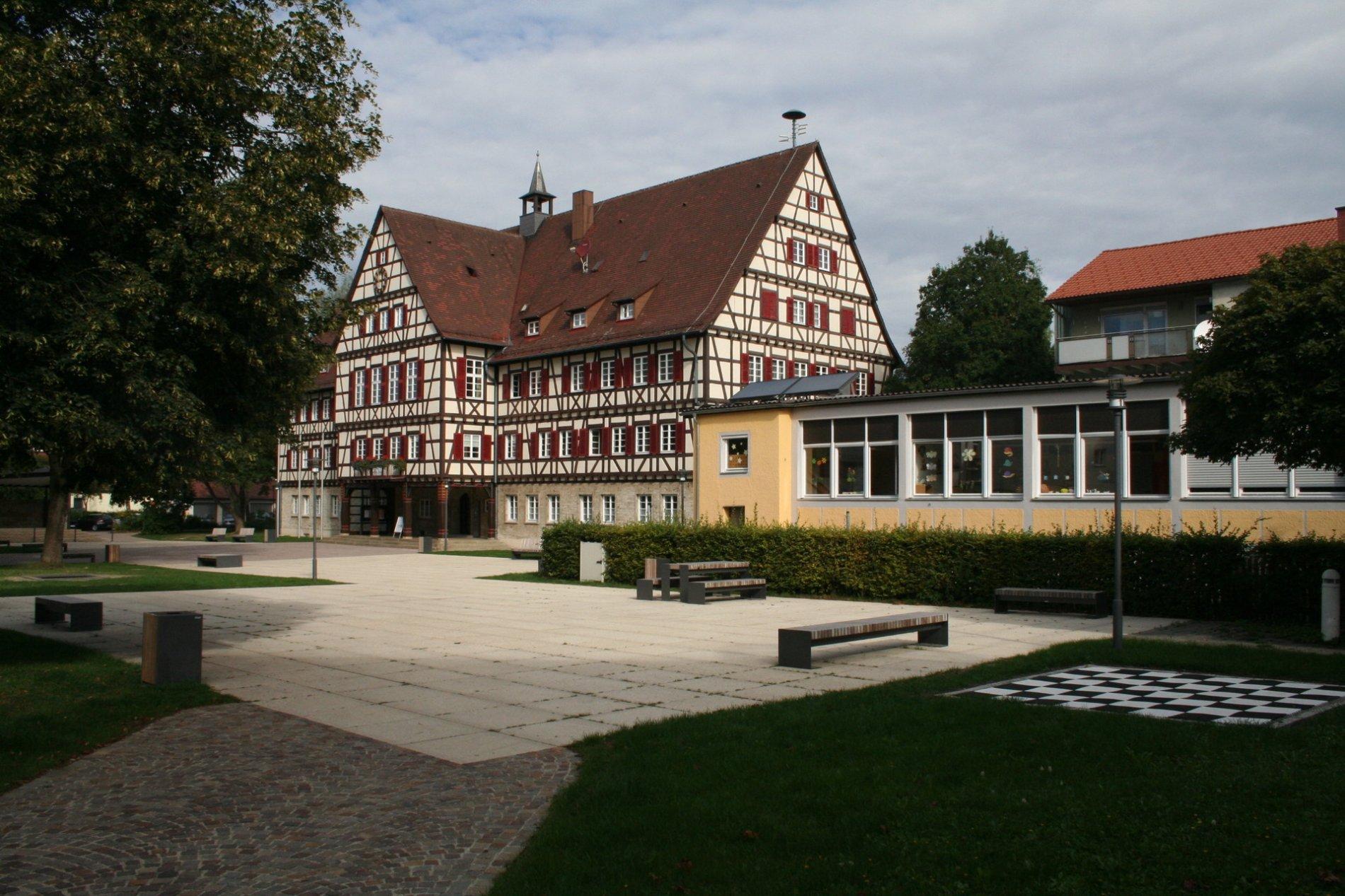 ein großer asphaltierer Platz vor einem Fachwerkhaus mit roten Fensterläden , es gibt verschiedene Sitzgelegenheiten aus Holz, auf der rechten Seite ist ein Schachbrett