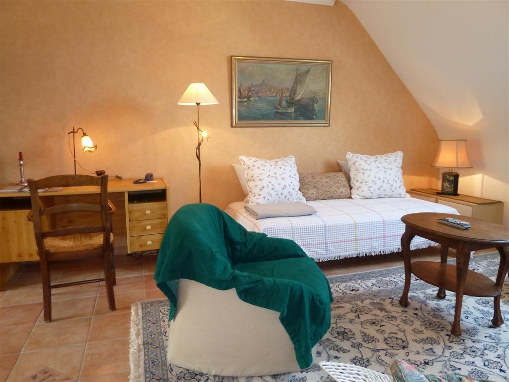 Wohnzimmer mit gemütlichen Sitzgelegenheiten und einem Schreibtisch