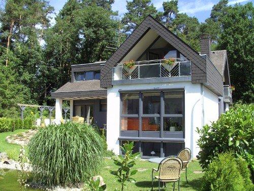Rückansicht der Ferienwohnung mit Garten, Fensterfront, Tisch und zwei Stühle