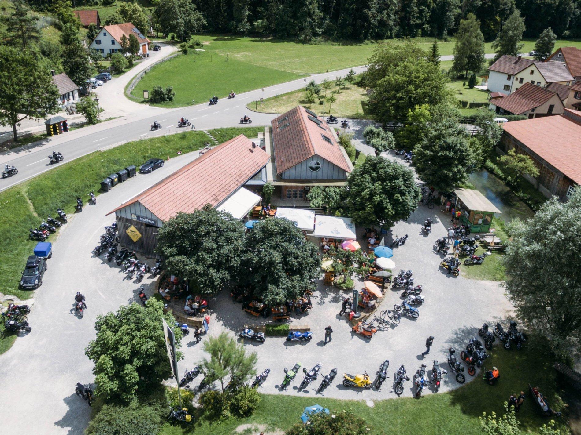 Bootshaus von oben. Auf dem Parkplatz stehen Personen und Motorräder.