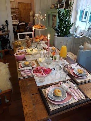 Ein liebevoll gedeckter Esstisch mit sechs Plätzen. Neben Geschirr befindet sich auch Gebäck, Wurst und Käse, Saft und zwei Kerzen darauf.