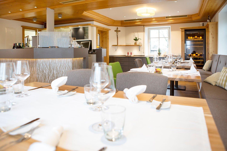 Ein Raum mit mehreren gedeckten Tischen und Stühlen. Er ist gemütlich modern eingerichtet.