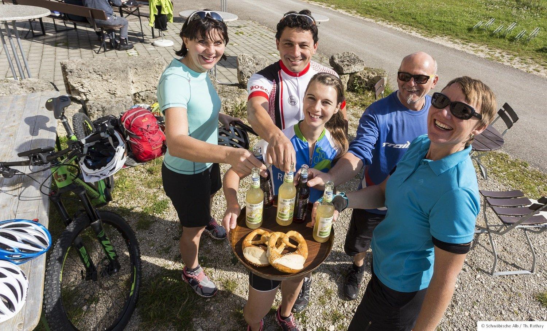 Fünf sportlich kurz gekleidete Personen stehen um ein Tablett mit Brezeln und Getränken. Sie lächeln in die Kamera.