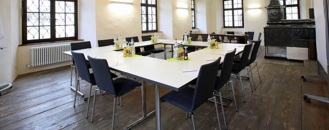 Ein Raum mit mehreren Tischen, die zum Quadrat zusammen gestellt sind. Ringsherum sind mehrere Stühle.