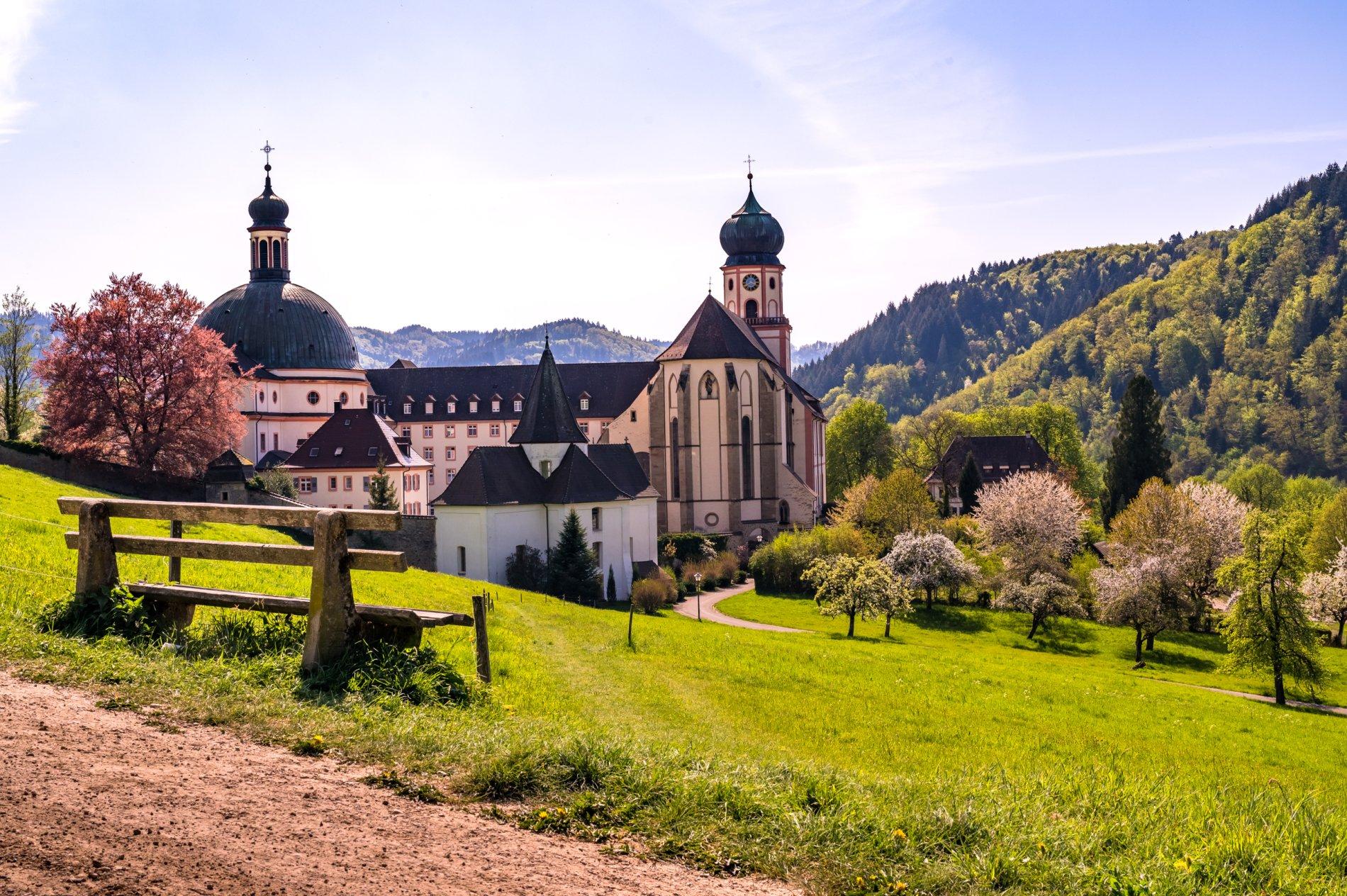 Blick auf eine weitläufige Wiese, im nahen Hintergrund das Kloster aus der Seitenansicht
