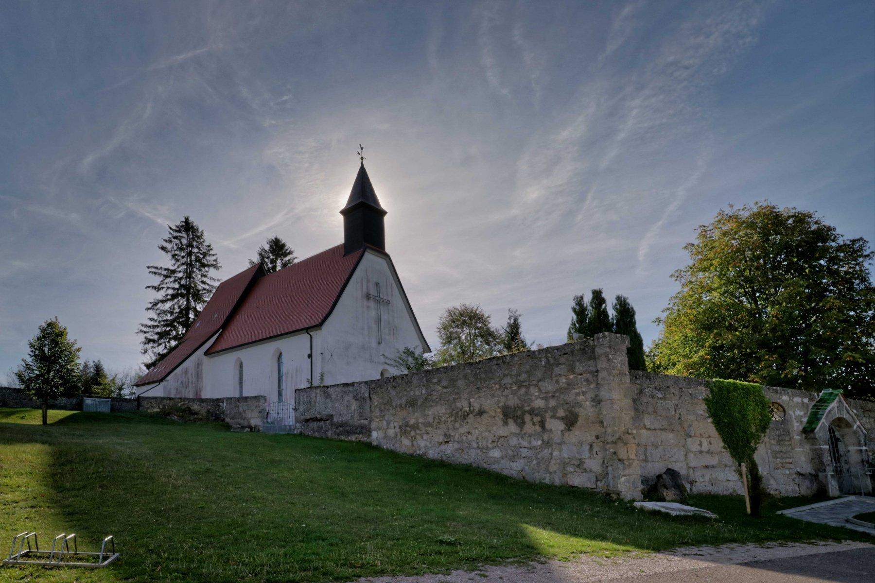 Eine Kirche, hinter deren Kirchturm die Sonne strahlt. Die Kirche hat ein großes Kreuz auf der Fassade. Davor ist eine Steinmauer.