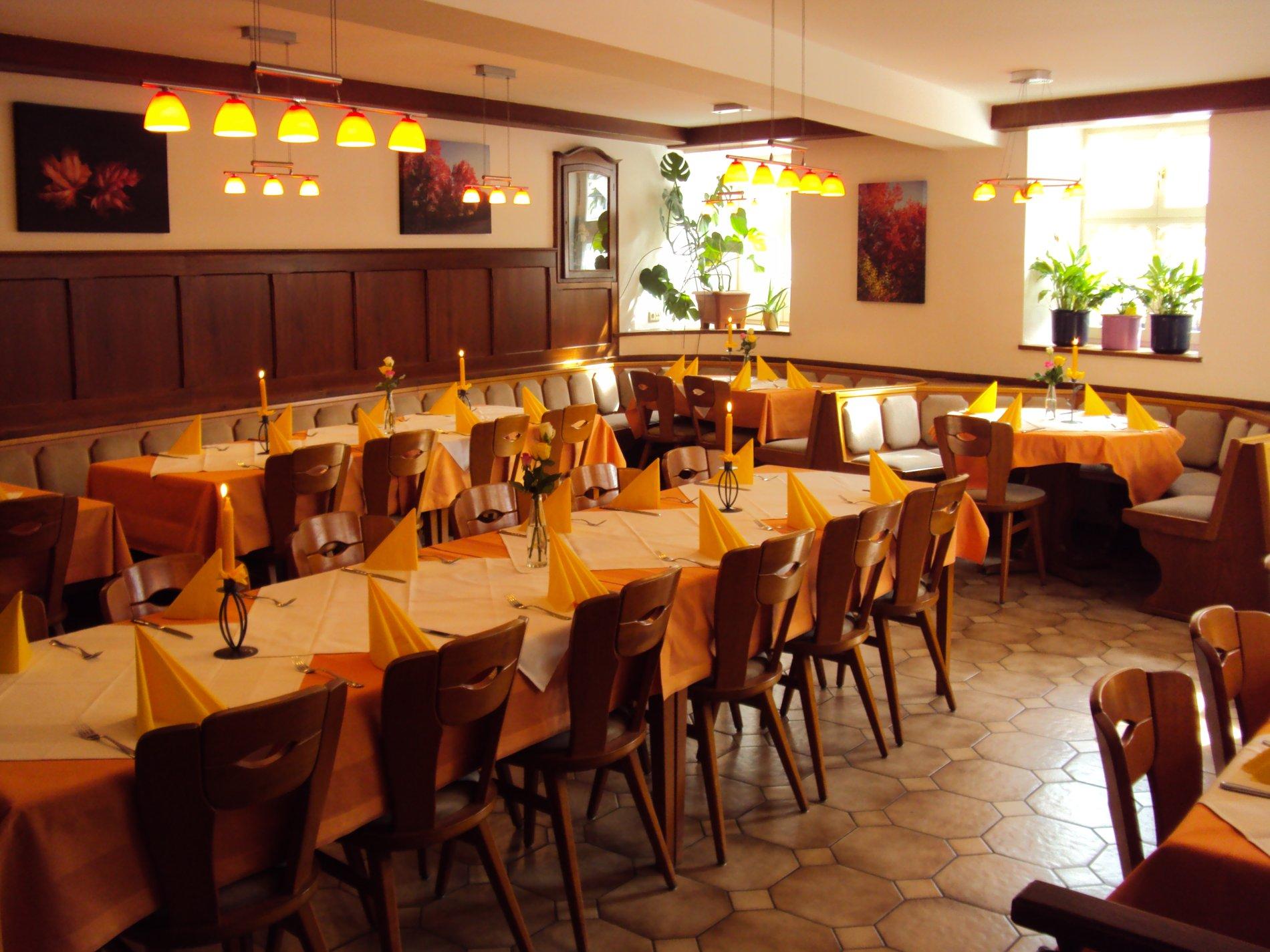 Ein Raum mit mereren Tischen, Stühlen und Bänken. Er ist stimmungsvoll beleuchtet und durch das Holz rustikal.