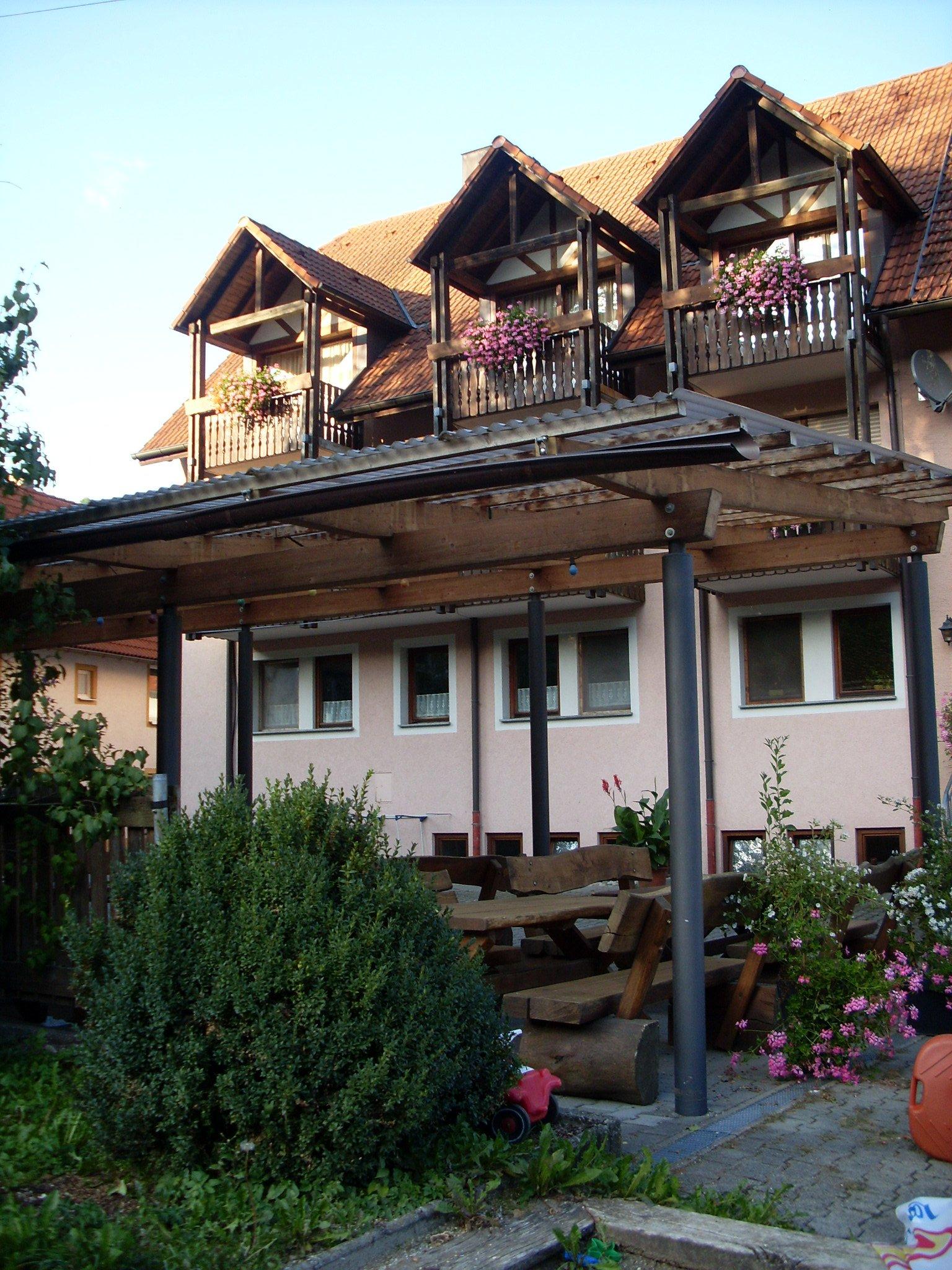 Gasthof zum Rössle von der Rückseite. Am Balkon hängen in Geranien in Blumenkästen.Vor dem Haus ist eine überdachte Terrasse mit Tisch und Bänken aus Holz.