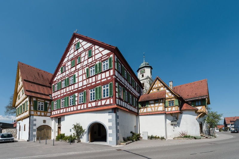 Ein großes historisches Fachwerkhaus von außen mit vielen Fenstern und grünen Fensterläden. Der Himmel ist strahlend blau.