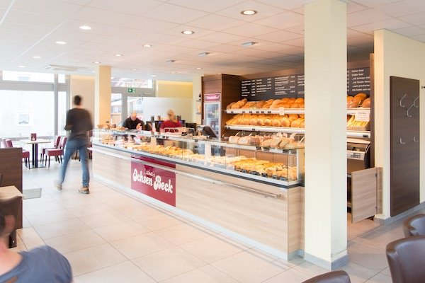 Eine Bäckereitheke mit der Aufschrift Ochsen Beck, in der viele Backwaren ausgelegt sind. Dahinter ist eine große Auslage mit Brot. Drumherum sind einige Personen und Tische und Stühle.