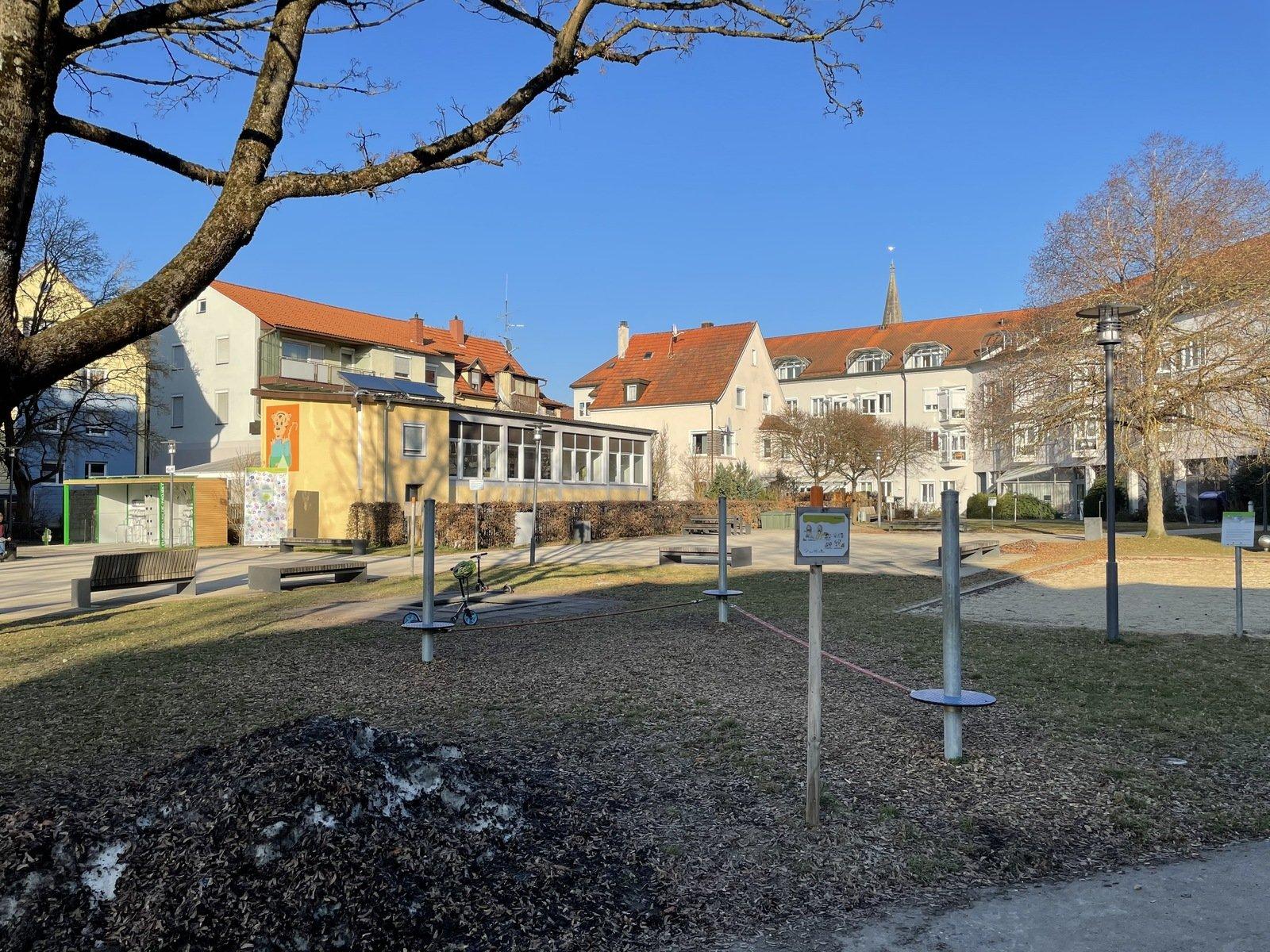 Ein Spielplatz mit einer Slack-Line, im Hindergrund sind Holzbänke zum verweilen