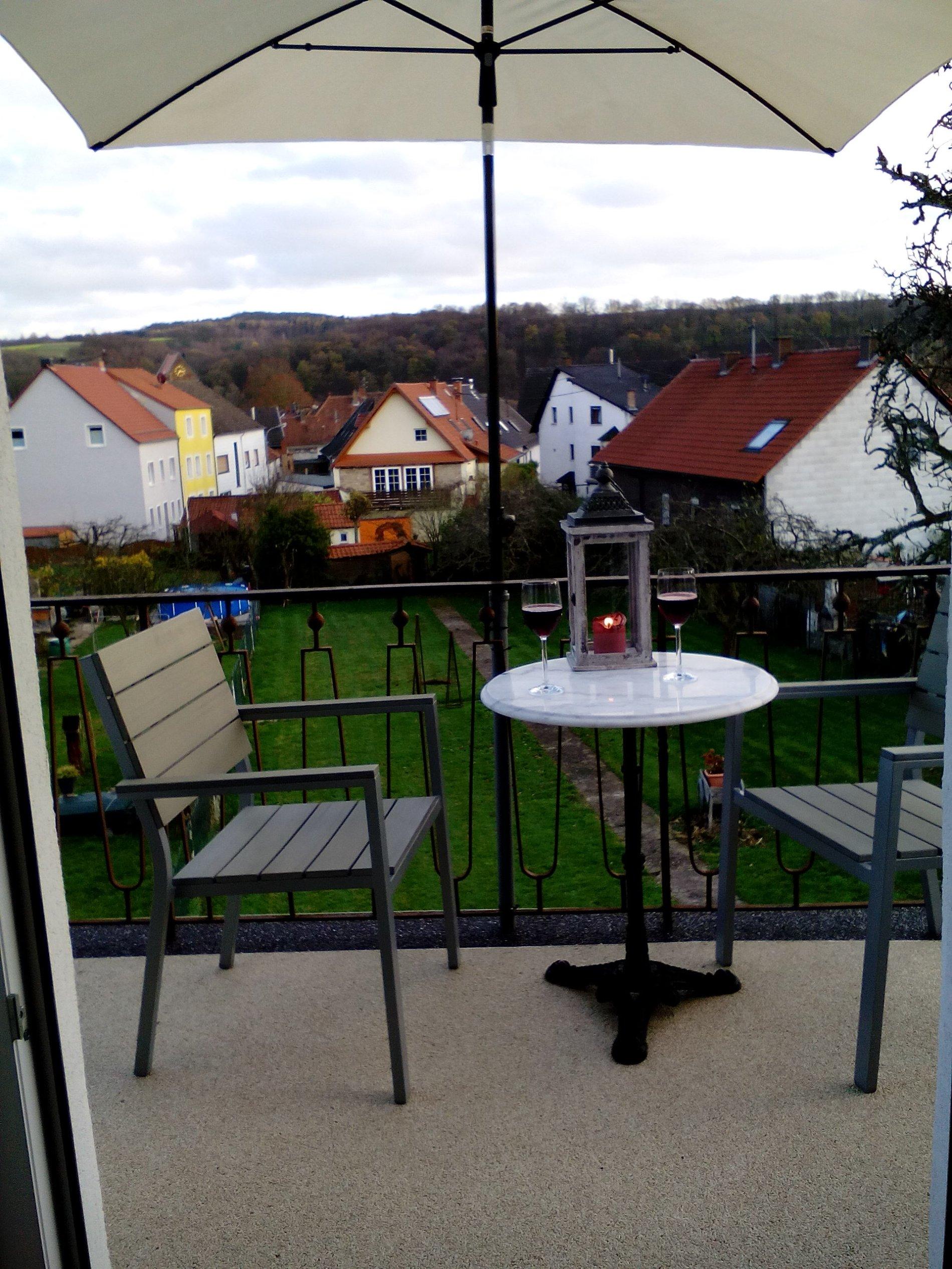 Balkon mit 2 Stühlen und einem kleinen Tisch mit Aussicht aufs Dorf