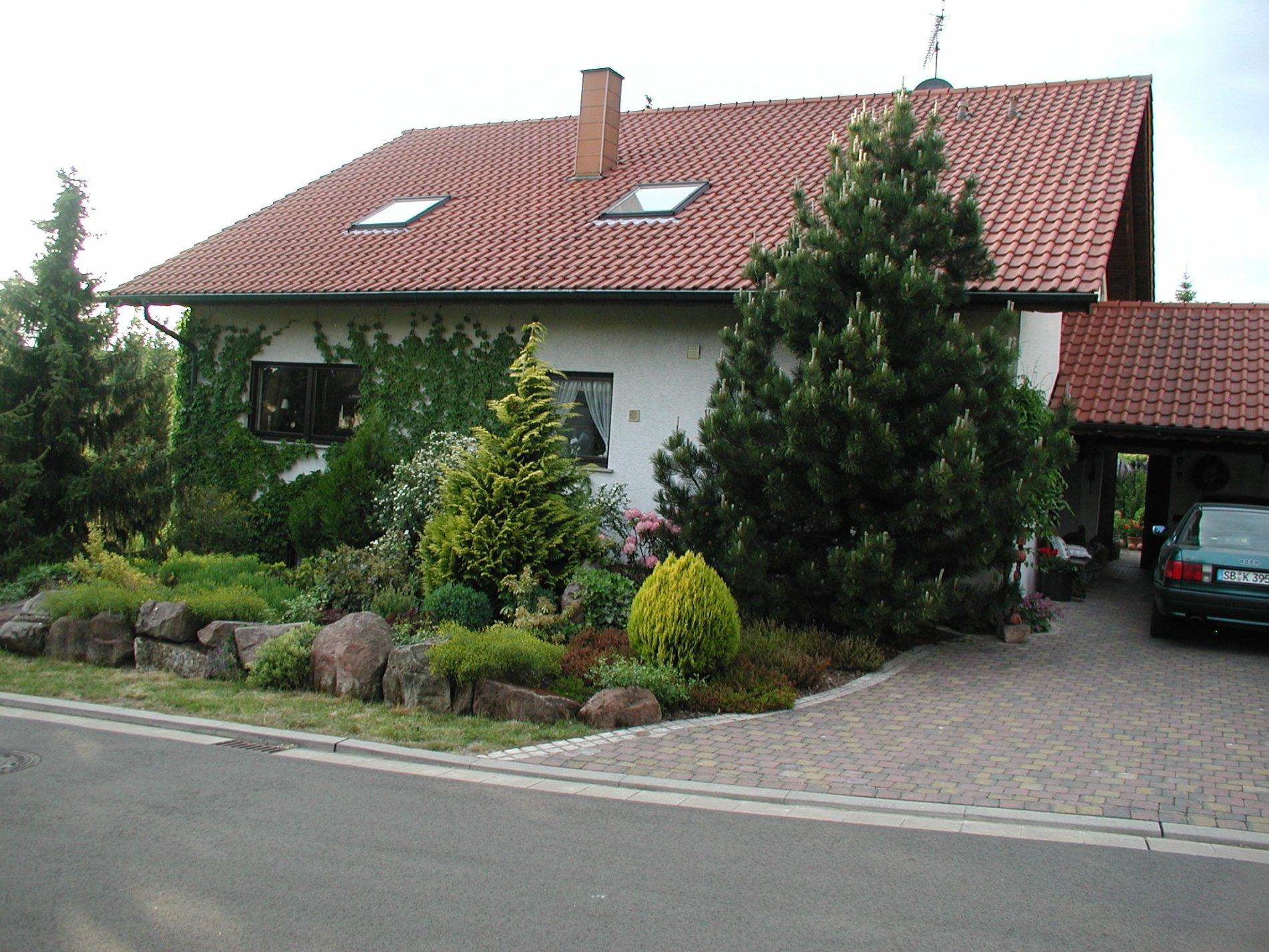 Die Ferienwohnung von außen mit grünem Vorgarten und einer Einfahrt