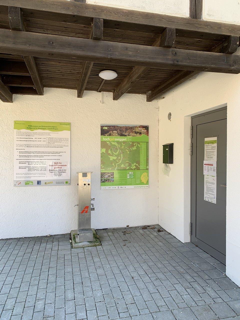 Eine Wandertafel und eine Infotafel sind an einer Hütte an der Wand unter einem Vordach angebracht. Dazwischen steht eine Entsorgungsstation für Wohnmobile.