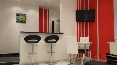 Küchentheke mit schwarzen Hockern und rot-weißen Wänden