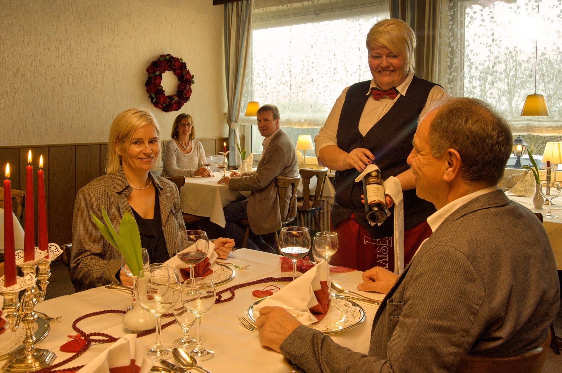Bedienung empfiehlt den Gästen eine Flasche Wein