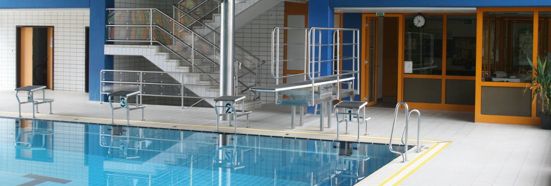 Ein Schwimmbecken in einer Halle, an dessen Ende mehrere Sprungbretter und Sprungblöcke. Dahinter ist eine Treppe.