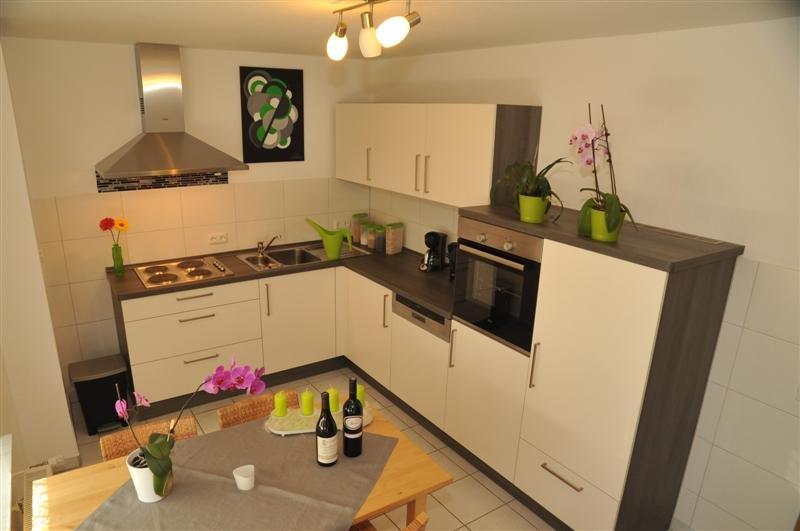 Weiße moderne Küche mit Küchentisch und Fliesenboden