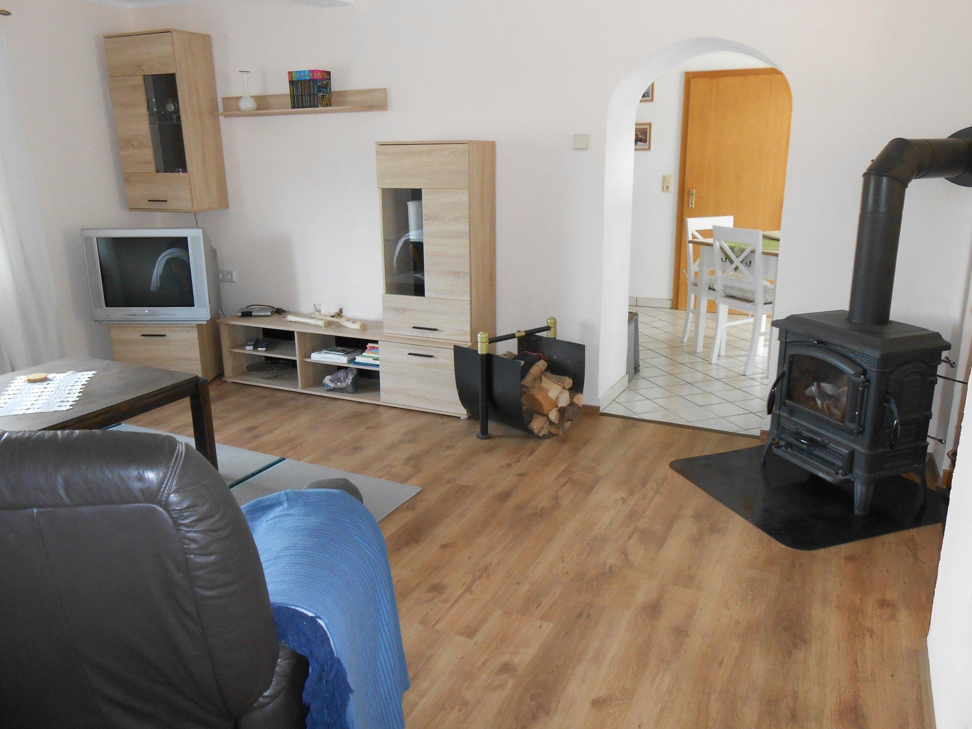 Helles Wohnzimmer mit einem Ofen und Fernsehwand