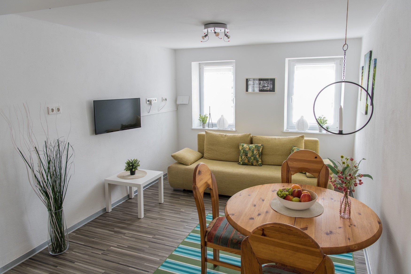 Gelbe Couch, Tisch mit 3 Stühlen, Fernseher auf Laminatboden