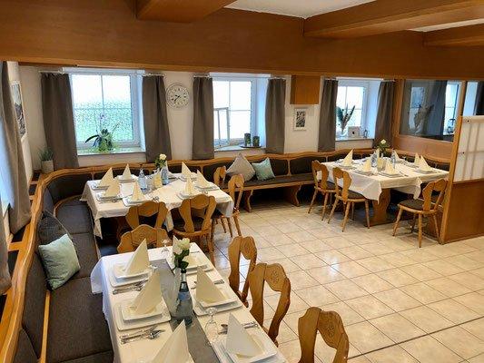 Ein Raum mit rustikalen Balken an der Decke, mehreren gedeckten Tischen und Stühlen.