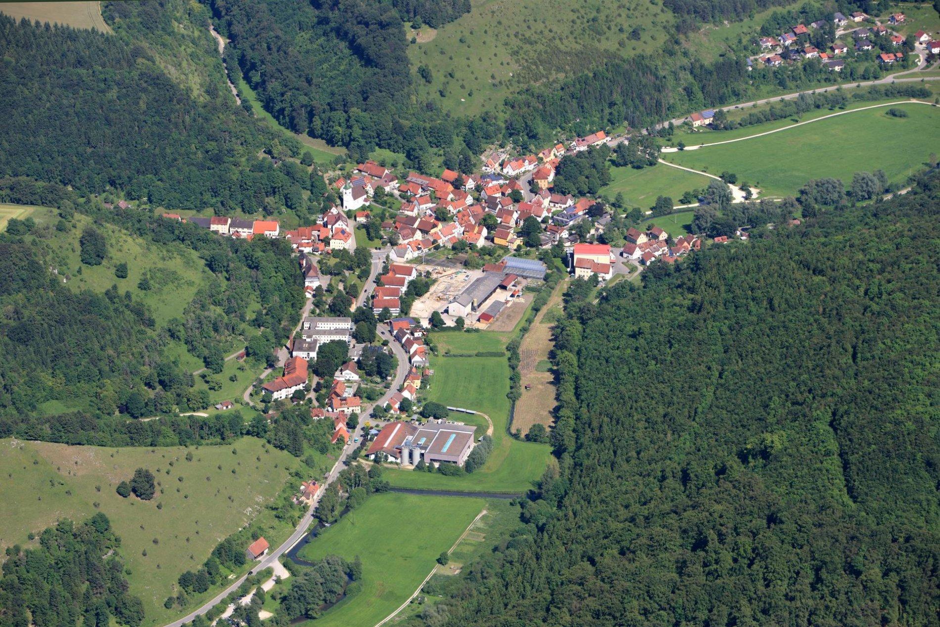 Ein Luftbild von einem Dorf, durch das ein Fluss fließt. Ringsherum sind bewaldete Hügel.