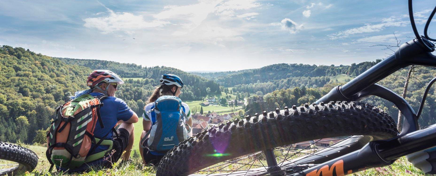 Zwei Radfahrer*innen sitzen auf einem Hügel und blicken lächelnd ins Tal. Im Vordergrund liegt ein Mountainbike. Der Himmel ist strahlend blau und die Farben leuchten.