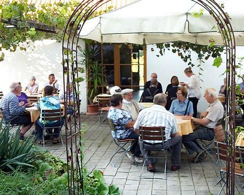 Eine sommerliche Terrasse mit Sonnenschirmen, Tischen und Stühlen. Alle Tische sind besetzt.
