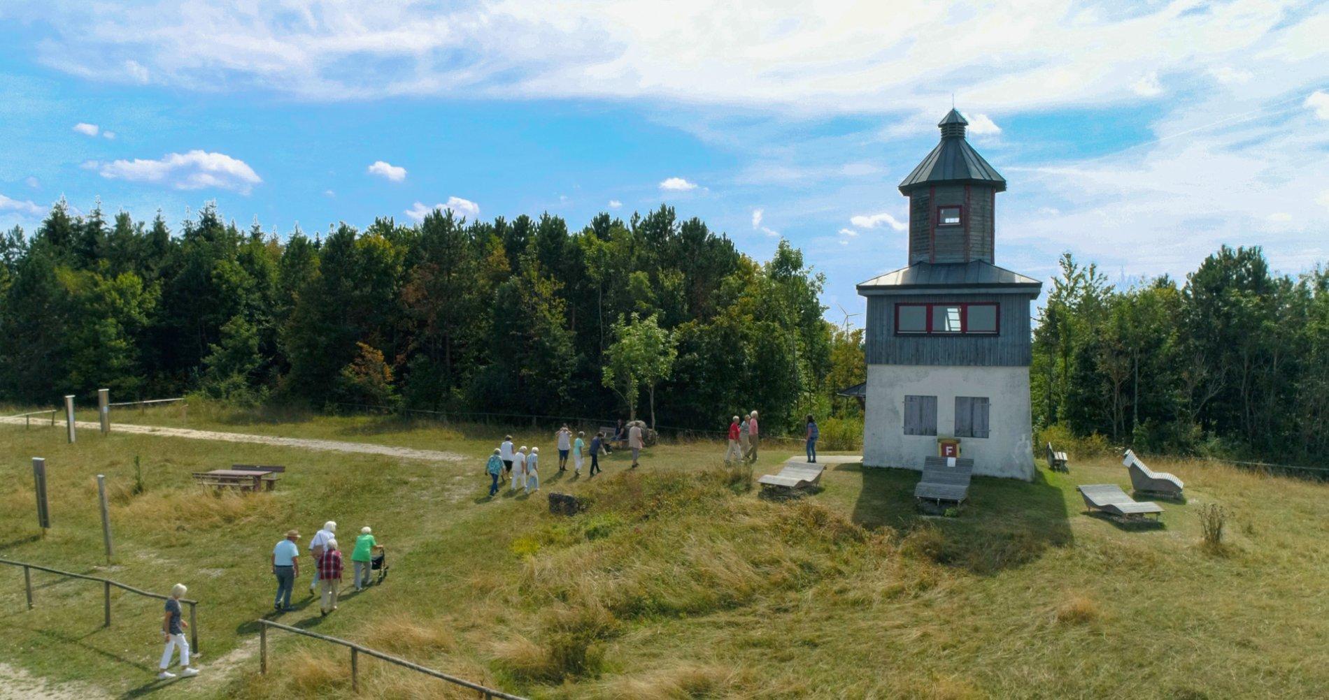 Eine Gruppe von Menschen läuft zum weiß-blauen Turm. Rund um den Turm stehen Holzliegen. Dahinter ist Wald. Am Himmel sind vereinzelt Wolkenschleier.