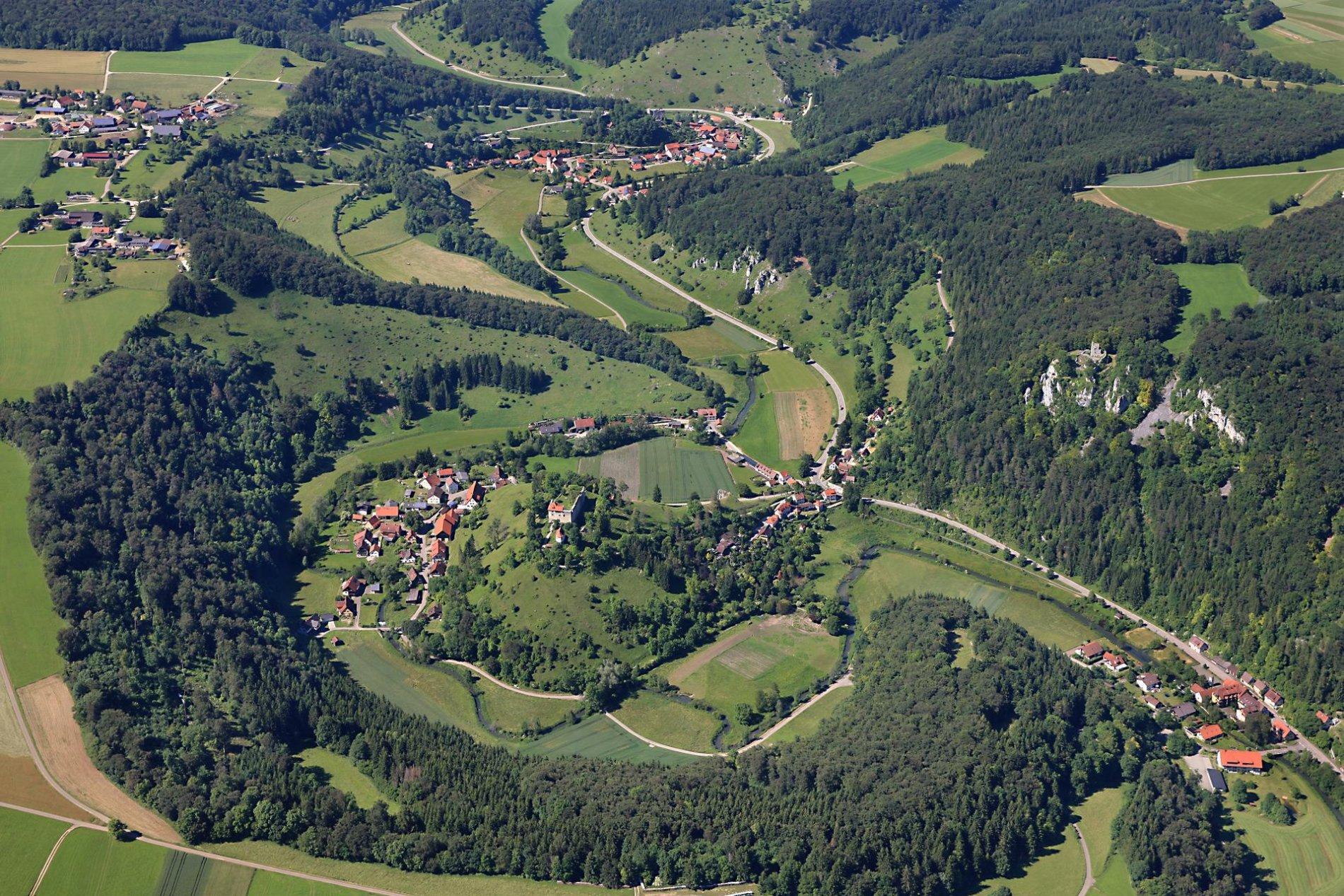 Ein Luftbild von mehreren Häusern, einem Fluss und zwei Burgen. Ringsherum sind Felder und Wälder.